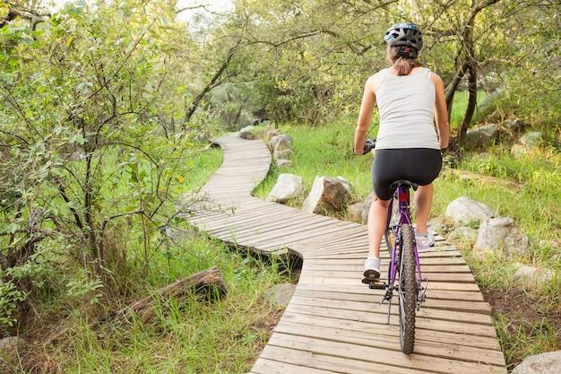 Achtermening van het atletische donkerbruine berg biking op houten weg