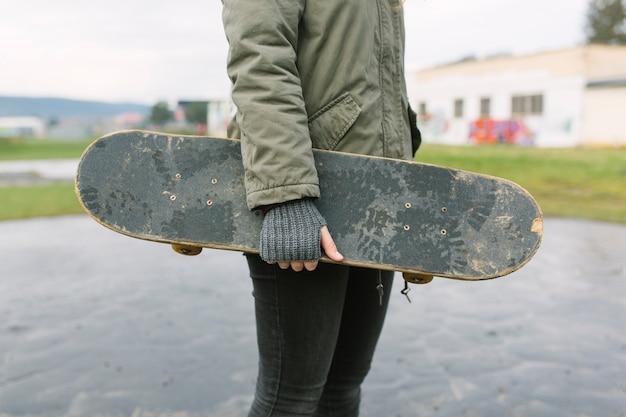 Achtermening van het skateboard van de vrouwenholding