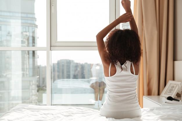 Achtermening van het uitrekken van vrouw thuis in de ochtend