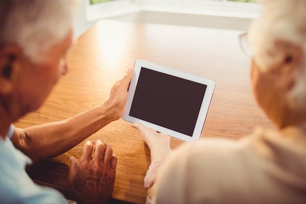 Achtermening van hoger paar die tablet thuis gebruiken