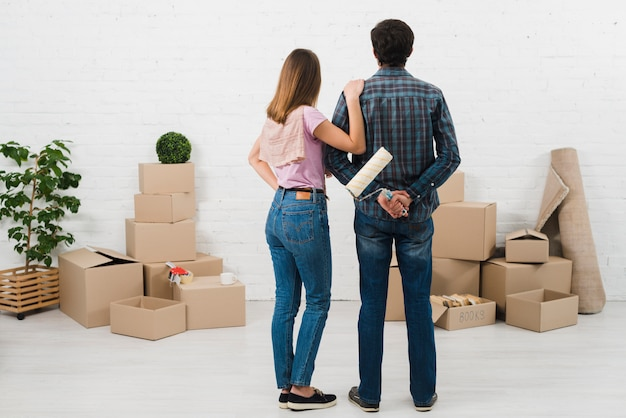 Achtermening van jong paar die de witte geschilderde muur met kartondozen bekijken