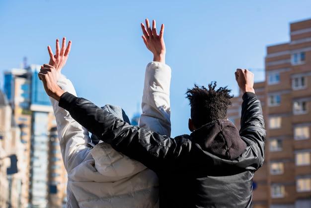Achtermening van jong paar die tussen verschillende rassen hun wapens opheffen die stadshorizon bekijken