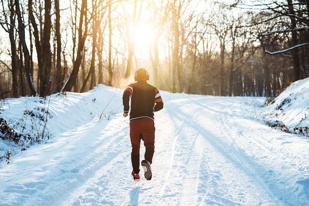 Achtermening van jonge atletische agent in sportkleding met hoofdtelefoons die in het winterse bos in de ochtend lopen.