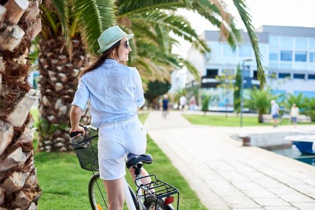 Achtermening van jonge gelukkige vrouw die een fiets berijden op groene palm op heldere zonnige dag