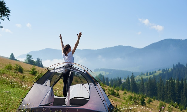 Achtermening van jonge gelukkige vrouw die zich met opgeheven wapens op bloeiende heuvel bij kleine toeristentent onder mooie duidelijke blauwe hemel op heldere de zomerochtend bevinden. toerisme en kamperen concept.