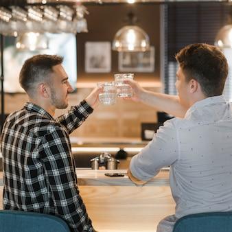 Achtermening van jonge mensen roosterende dranken in de bar