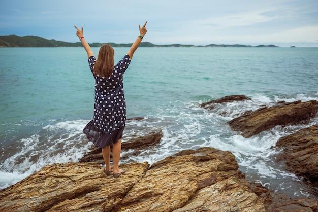 Achtermening van jonge vrouw die zich op de rots opgeheven handen omhoog bij het strand bevinden.