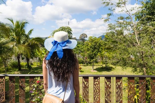 Achtermening van jonge vrouw in hoed en kleding
