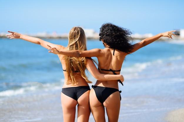 Achtermening van jonge vrouwen met mooie organismen in bikini die pret op een tropisch strand hebben.