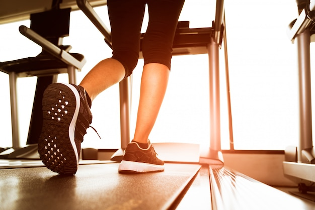 Achtermening van lagere lichaamsbenen van geschiktheidsmeisje die op machine of tredmolen in geschiktheidsgy lopen