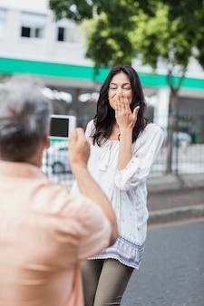 Achtermening van man die vrouwen blazende kus fotograferen