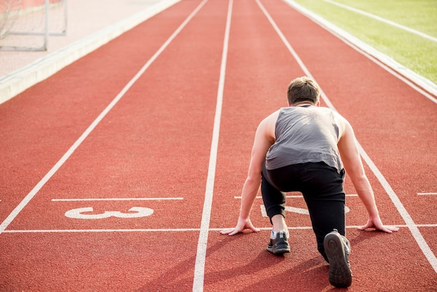 Achtermening van mannelijke atleet klaar om de relaisrace op renbaan te beginnen