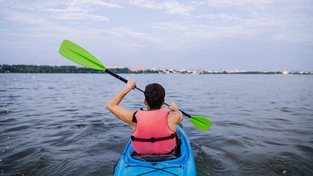 Achtermening van mannelijke kayaker paddelende kajak