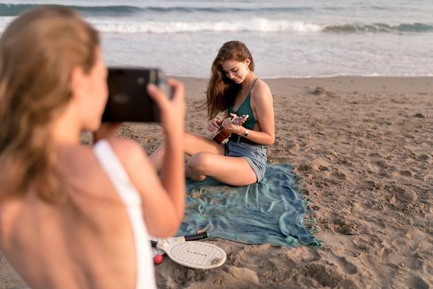 Achtermening van meisje die foto van een meisjes spelende ukelele nemen bij strand van onmiddellijke camera