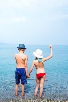Achtermening van meisje en jongensholdingshanden bij de kust.
