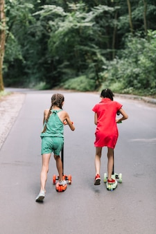 Achtermening van meisjes berijdende duwautopedden op weg