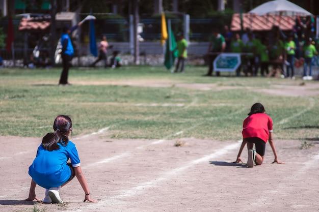 Achtermening van meisjesstudenten klaar om op renbaan op een sportdag te lopen