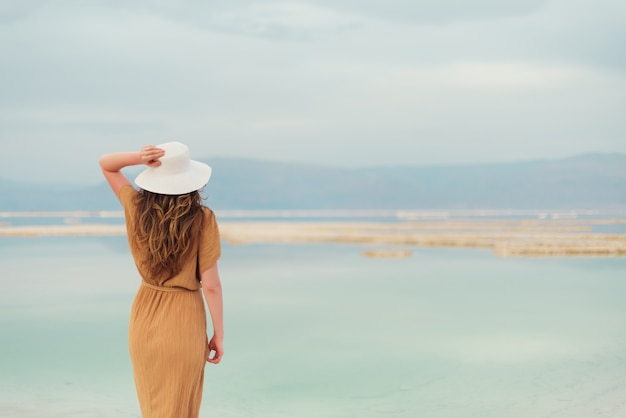 Achtermening van modieus meisje die kleding op kust dragen