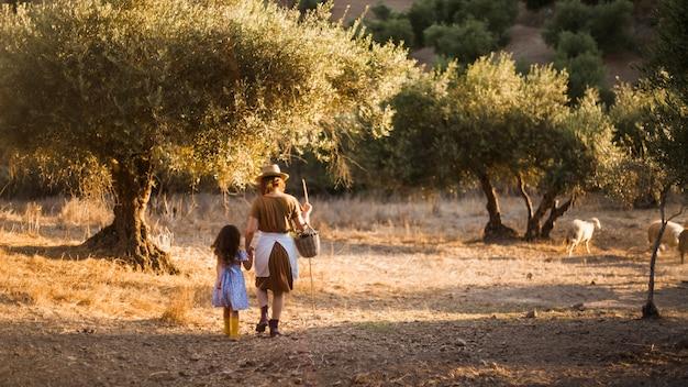 Achtermening van moeder en haar dochter die op het gebied lopen