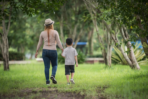 Achtermening van moeder en zoon die samen in de holdingshand van de huistuin lopen.
