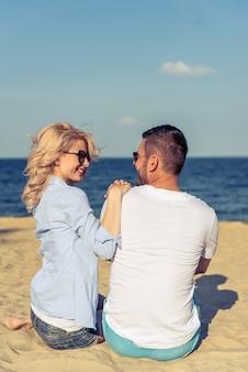 Achtermening van mooi jong paar op strand.