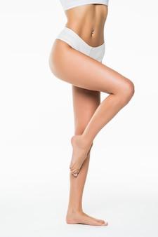 Achtermening van mooie vrouw met lange benen, die op witte muur wordt geïsoleerd