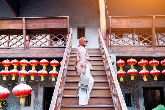 Achtermening van moslimvrouwentoerist die zich op een trap in een chinese huisatmosfeer bevinden, aziatische vrouw in vakantie. reizen concept. chinees thema.