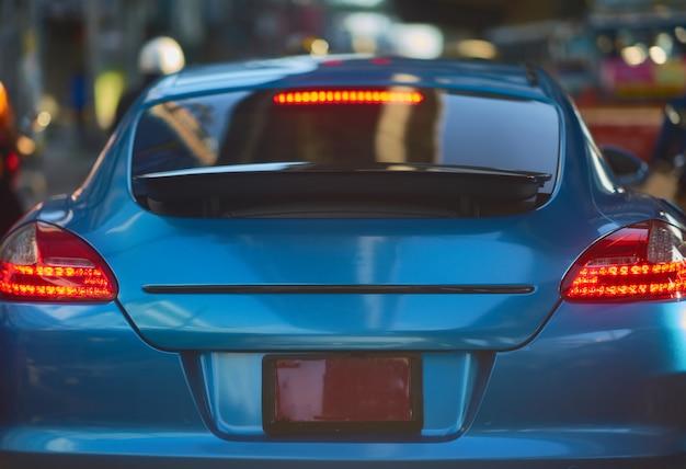 Achtermening van nieuwe sportwagen op de achtergrond van de verkeersstraat