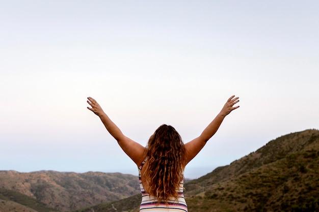 Achtermening van onbezorgde vrouw in openlucht met omhoog handen