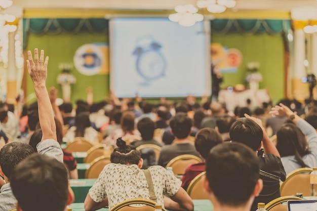 Achtermening van publiek die hand tonen om de vraag van spreker op het stadium te beantwoorden