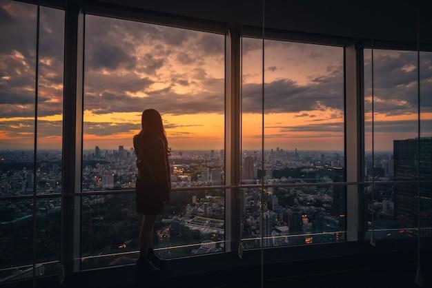 Achtermening van reizigervrouw die de horizon van tokyo en mening van wolkenkrabbers op het observatiedek kijken bij zonsondergang in japan.