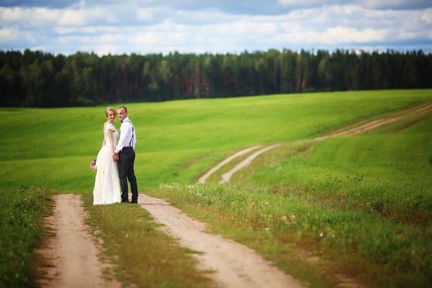 Achtermening van romantisch paar van bruid en bruidegom die hand in hand op landelijke weg lopen.