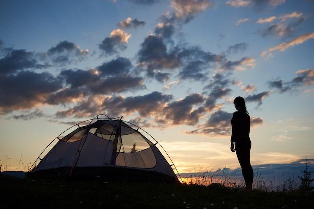 Achtermening van silhouet van meisje die backpacker zich bovenop berg bevinden