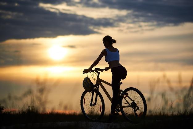 Achtermening van slanke vrouwelijke fietsers die bij fiets en het stellen zitten. sportieve vrouw op de fiets, genietend van en genietend van een fantastisch en fantastisch uitzicht op zonsondergang en landschap.