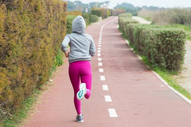 Achtermening van sportieve vrouw in roze beenkappen die over spoor lopen