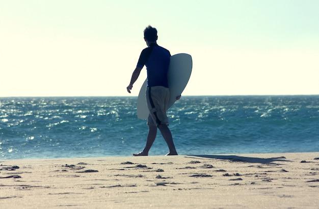 Achtermening van surfer met surfplank die golven bekijkt