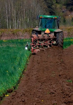 Achtermening van tractor die en de aarde op landbouwbedrijf graven bewerken die voor het planten voorbereidingen treffen