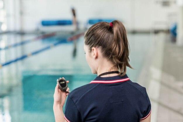 Achtermening van trainer die chronometer bij de pool bekijken