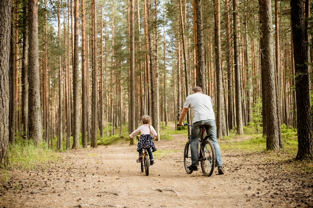 Achtermening van vader en dochter berijdende fietsen rond bos. jong gezin in de zomer het cirkelen in park. de themafamilie sport openluchtrecreatie. avontuurlijke recreatieconcept.