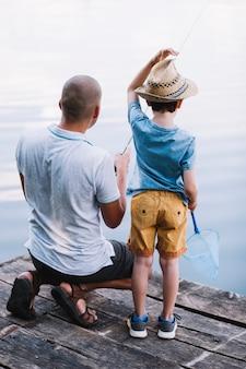 Achtermening van vader en jongen die in het meer vissen