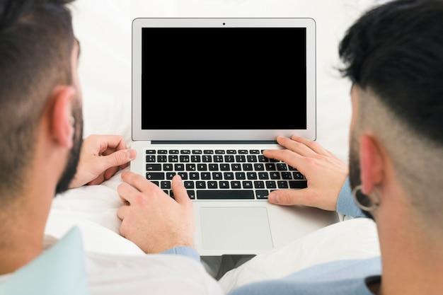 Achtermening van vrolijk paar die de digitale tablet op bureau gebruiken