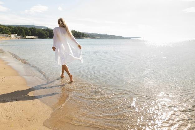 Achtermening van vrouw die van het strandzand genieten