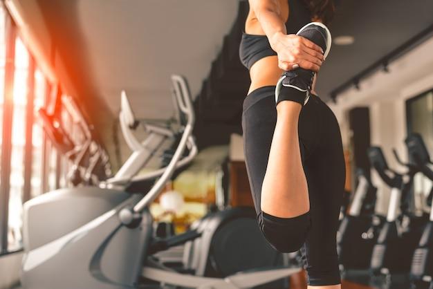 Achtermening van vrouw die yoga in fitness sport opleidingsclub doen met sportmateriaal