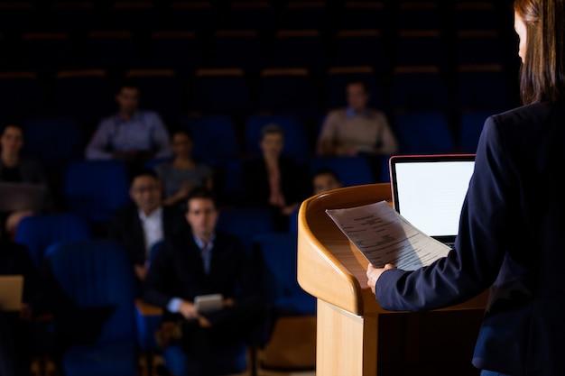 Achtermening van vrouwelijke directeur die een toespraak houdt