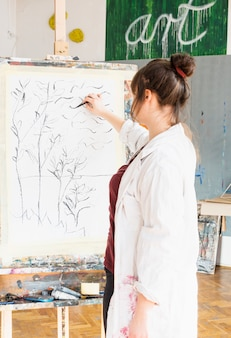 Achtermening van vrouwelijke kunstenaarstekening op canvas met houtskoolstok