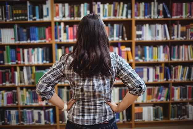 Achtermening van vrouwelijke student die boeken in de plank bekijkt