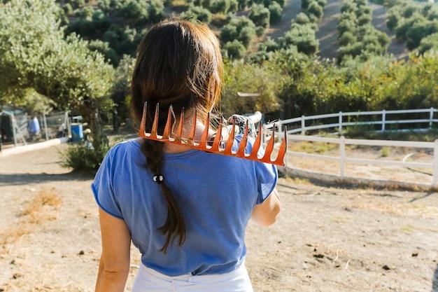 Achtermening van vrouwen dragende hark op haar schouder op het gebied