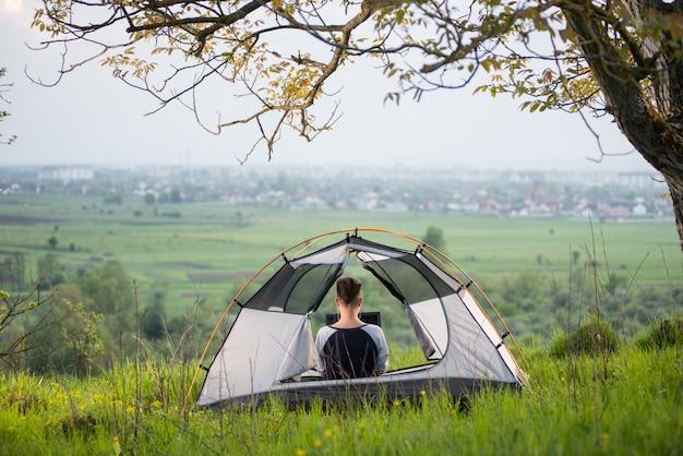 Achtermening van vrouwenzitting in een tent bovenop een heuvel die haar laptop met behulp van terwijl het kamperen