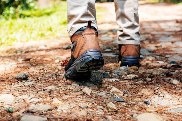 Achtermening van wandelaarsmens met laarzen het lopen