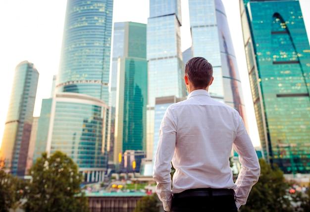 Achtermening van zakenman die op exemplaarruimte kijken terwijl status tegen glaswolkenkrabber